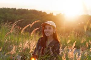 Portrait Asian woman backpacking. She was smiling and happy to travel at sunrise seaside mountain peak photo