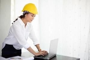 Asian women engineering inspecting and working and holding blueprints at office photo