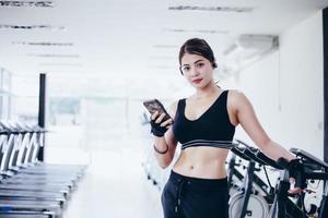 atleta asiático en ropa de moda de ropa deportiva. deportista escuchando música usando la aplicación de teléfono para el rastreador de actividad física: monitor de frecuencia cardíaca que rastrea su progreso de salud en el teléfono inteligente. foto