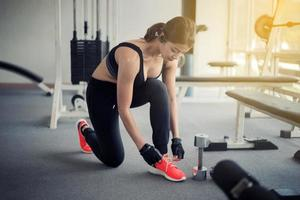 women asian tying shoe laces. fitness women getting ready for engage in the gym photo