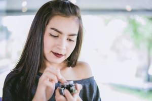 A beautiful woman asian using a skin care product, moisturizer or lotion taking care of her dry complexion. Moisturizing cream in female hands . photo