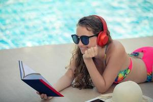 Women wear bikinis, read books and listen to music at the summer recreation pool. photo