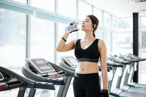 Sporty woman asia drinking water after exercises in the gym. Fitness - concept of healthy photo