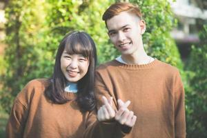 Hermosa joven pareja haciendo forma de corazón con las manos y sonriendo feliz en el amor al aire libre foto