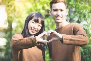 Beautiful young couple making heart shape with hands and Smiling happy in love outdoors photo