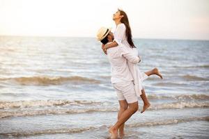 Feliz pareja romántica amante tomados de la mano juntos caminando por la playa foto