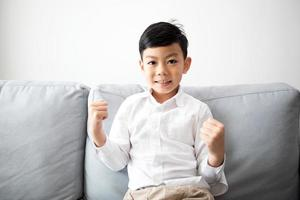 Excited and Happy family and son with arms raised while watching television at home photo