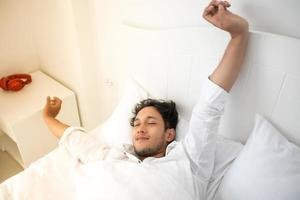 A man waking up in her bed fully rested and open the curtains in the morning to get fresh air. photo