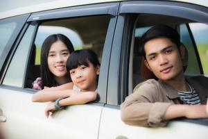 Happy little girl  with asian family sitting in the car for enjoying road trip and summer vacation in camper van photo