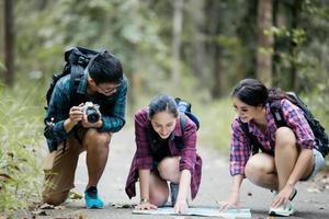grupo asiático de jóvenes de excursión con amigos mochilas caminando juntos y mirando el mapa y tomando la cámara de fotos en la carretera y mirando feliz, tiempo de relax en concepto de vacaciones viajes