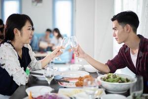 Pareja joven asiática disfrutando de una cena romántica con bebidas por la noche mientras está sentado en la mesa del comedor en la cocina juntos, enfoque suave foto