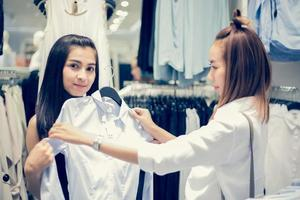 Two smiling young woman Asian with shopping and buy at mall supermarket photo
