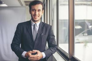 Happy handsome businessman standing and smiling in office photo