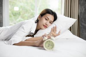 Mujer asiática feliz despertando y apagando el despertador teniendo un buen día foto