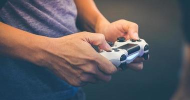 Hombres asiáticos amigos competitivos jugando videojuegos y emocionados felices alegres en casa foto