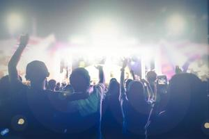 silhouettes of concert crowd at Rear view of festival crowd raising their hands on bright stage lights photo