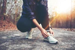 woman tying shoe laces for sport fitness runner getting ready for jogging outdoors on forest path in late summer or fall. photo