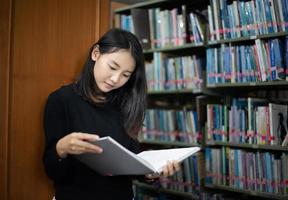 Asian students reading books in the library. photo
