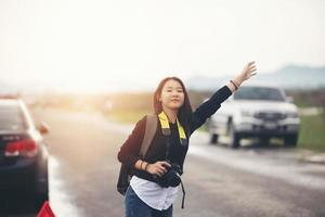 mujeres jóvenes asiáticas personas que caminan con mochilas estresadas después de una avería de automóvil con un triángulo rojo de un automóvil en la carretera y una mujer de pie con los brazos levantados al borde de la carretera. foto