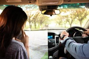 Asian man and woman using mobile on road trip and Happy young couple with a map in the car. Blurred and Soft focus photo