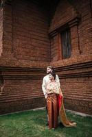 La novia asiática y el novio caucásico tienen tiempo romántico con el vestido de Tailandia foto