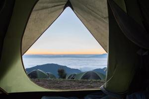 View from tent entrance on beautiful mountain sunrise photo