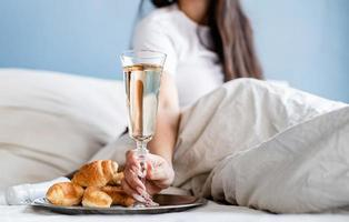 Young brunette woman sitting awake in the bed with red heart shaped balloons and decorations drinking champagne eating croissants photo