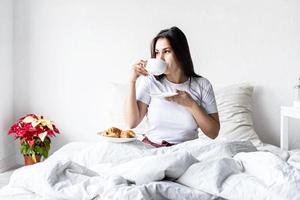 Young brunette woman sitting awake in the bed with red heart shaped balloons and decorations drinking coffee eating croissants photo