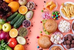 Frutas y verduras vs dulces y comida rápida vista superior plana sobre fondo naranja foto