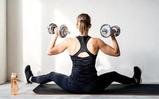 Rear view of young blond woman working out with dumbbells showing her back and arms muscles photo