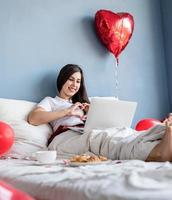 Young happy brunette woman sitting in the bed with red heart shaped balloons chatting with her boyfriend on laptop showing heart gesture with hands photo