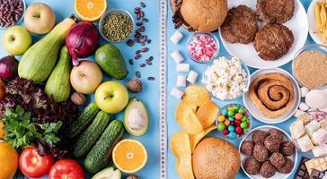 frutas y verduras vs dulces y comida rápida vista superior plana yacía sobre fondo azul foto