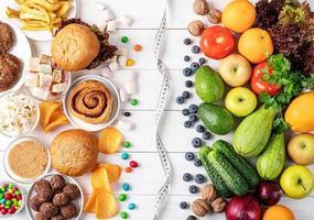 frutas y verduras vs dulces y comida rápida vista superior plana foto