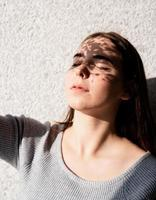 Portrait of a beautiful young woman with a shadow pattern on the face and body in the form of flowers photo