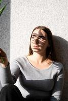 Portrait of a beautiful young woman with a shadow pattern on the face and body in the form of palm leaf photo