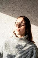 Portrait of a beautiful young woman with a shadow pattern on the face and body in the form of cotton photo