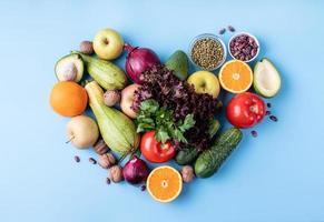 Frutas y verduras frescas en forma de corazón, vista superior plana yacía sobre fondo azul. foto
