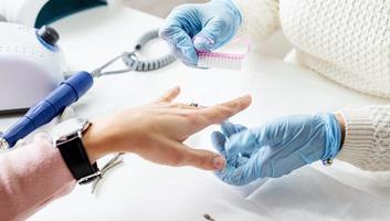 maestro de manicura usando un cepillo para limpiar el polvo después de quitar el esmalte en gel foto