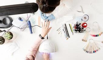 Maestro de manicura en máscara y guantes poniéndose esmalte de gel en las uñas de un cliente vista superior foto
