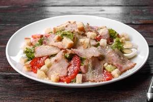 deliciosa ensalada fresca con tocino y tomates con especias y verduras foto