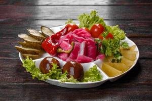 Delicious spicy pickles cut on a serving plate photo