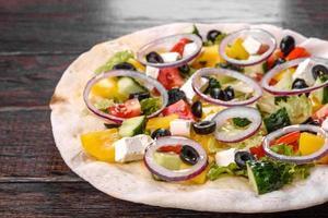 Sabrosa ensalada griega fresca en una pita cocinada para una mesa festiva foto