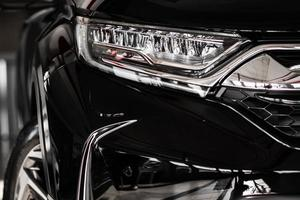 Modern luxury car close-up. Concept of expensive, sports auto. Headlight lamp of new cars,copy space. A modern and elegant car illuminated. photo