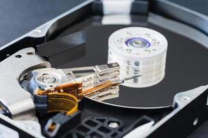 Unidad de disco duro desmontada dentro de primer plano, eje, brazo actuador, cabezal de lectura y escritura, plato foto