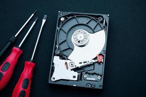 Vista superior del disco duro descubierto y destornilladores, inspección del hardware de la computadora foto
