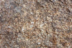 enfoque selectivo de piedra rústica y rugosa de granito marrón antiguo con detalle de textura. foto