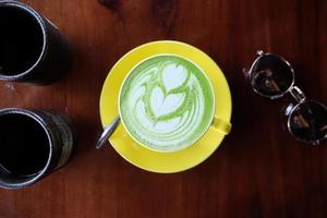 Vista superior de la espuma de arte latte de té verde matcha caliente foto