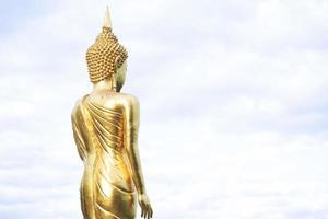 estatua dorada de buda de pie en una montaña, wat phra that khao noi foto