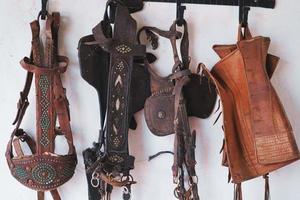 Bridas de caballo de cuero y brocas colgadas en la pared foto