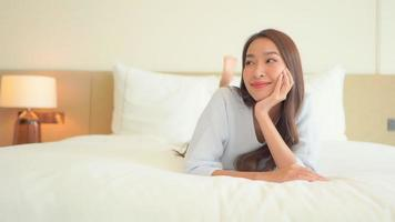 Asian woman relax on bed in bedroom interior video